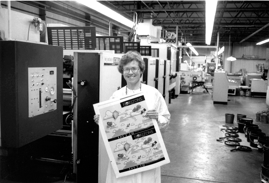 Barbara Roche holding printer proof of first Horizons magazine cover, featuring kites